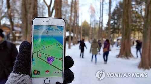 """口袋妖怪曾在世界范围内掀起游戏热潮。图为韩国玩家雪地""""捉妖""""。图片来源:韩联社"""